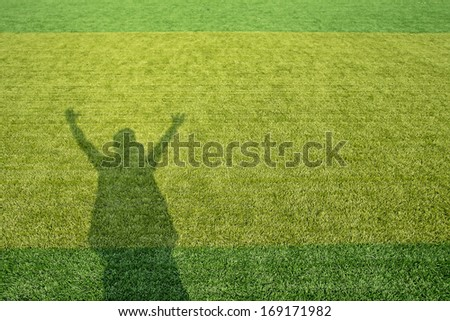 shadow of football coaches very happy on green field football .Positive human emotion - stock photo