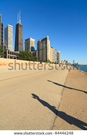 Shadow of male and female joggers running along Lake Michigan on Lakeshore Trail in the early morning in Chicago. - stock photo