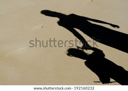 Shadow of mother and daughter walk on the beach over sand during summer vacation. Concept photo of: Mothers day, relationship, child care, childhood, motherhood. - stock photo