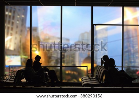 shadow of people at waiting chair on building background - stock photo