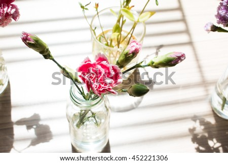 Shadow of pink flowers with sunshine on wood background.