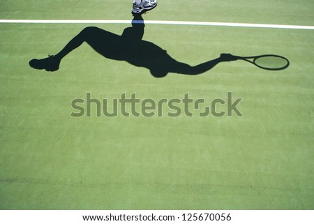 Shadow of tennis player on green tennis court - stock photo