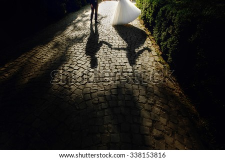 Shadow silhouette of beautiful bride and handsome groom dancing at sunset - stock photo