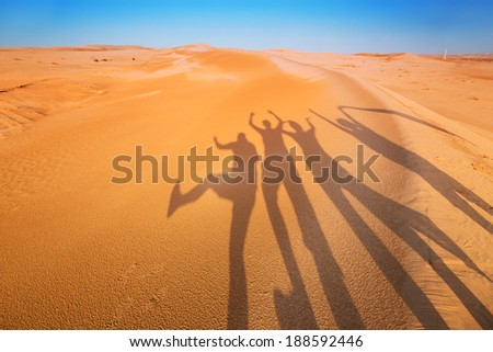 Shadow silhouettes of four people having fun in the desert  - stock photo