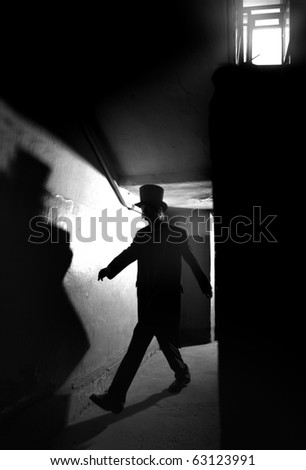Shadowgraph of the man in black coat and hat going in the dark interior. Monochrome photo with natural darkness. Artistic grain added for movie effect - stock photo