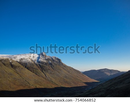 Shadows and Snow covered peaks in Langdale Valley Lake District