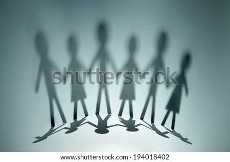 Shadows cast from chain of paper people - stock photo
