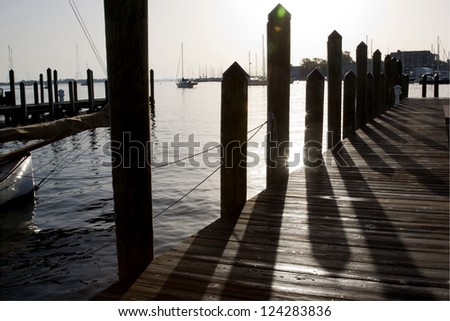 Shadows cast from the pilings onto the wooden planks of the city dock in the downtown area of Annapolis, Maryland in the early morning. - stock photo