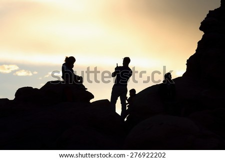 Shadows of a Family taking Pictures in the Mountains - stock photo