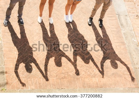 Shadows of friends holding and raising hands  together. They are two girls and two boys, the focus is on their shadows. Togetherness and friendship concepts with an unusual view. - stock photo