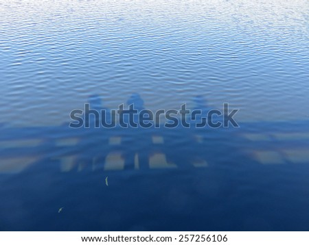 Shadows of People in Water on Observation Deck - stock photo