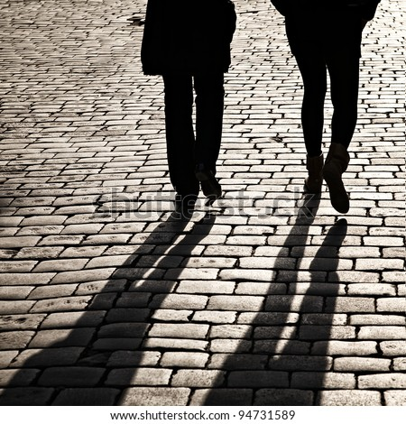 Shadows of people walking in a street of the city - stock photo