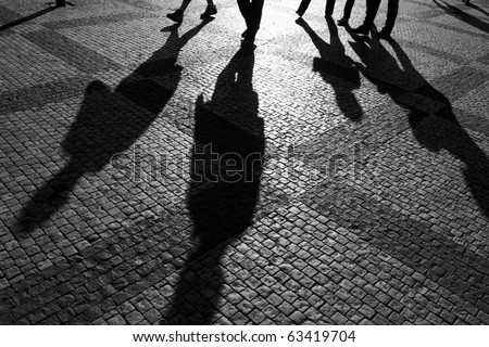 Shadows of people walking in a street of the city, Prague, September 2010. - stock photo