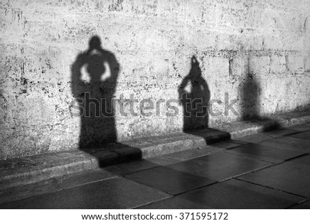 Shadows of praying people on temple wall in early morning - stock photo