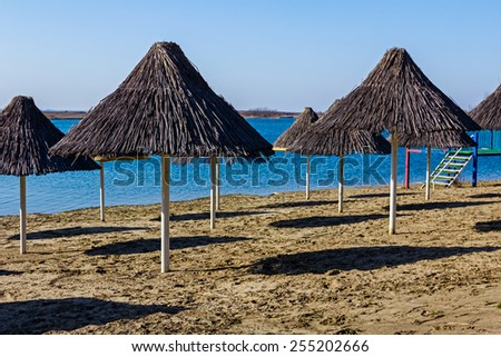 Shadows of reed umbrellas on an empty beach