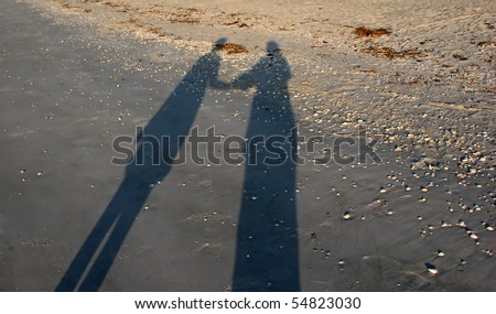 shadows two people holding hands morning sun beach - stock photo
