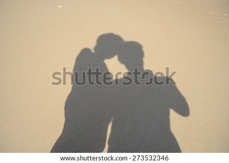Shadows two people on beach - stock photo