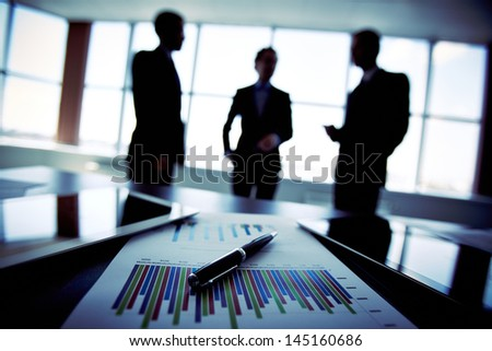 Shadowy business trio holding a briefing concerning the reported statistic data - stock photo