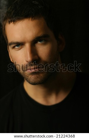 Shadowy dark close-up portrait of young good looking male model - stock photo