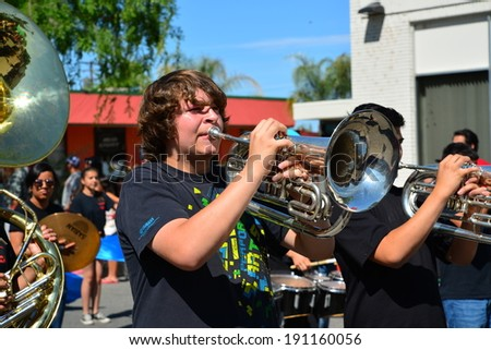SHAFTER, CA - MAY 3, 2014: The Shafter High School band brass section plays with enthusiasm on a hot day during the Cinco de Mayo Celebration parade. - stock photo