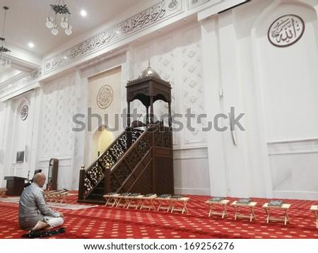 SHAH ALAM, SELANGOR, MALAYSIA-DEC.25: Unidentified muslim man prays inside a mosque in Shah Alam, Selangor, Malaysia on December 25, 2013. - stock photo