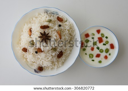 Shai Pulao or Vegetable Pulao or Indian Biryani or Pilaf or fried rice made of  Basmati rice in a white bowl served along with curd or raita on white background.a dish in Asia India,the Middle East - stock photo