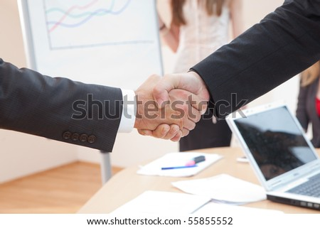 shake hands in the office with a laptop in the background