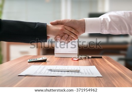 Shakehand of lawyer and business woman sitting behind desk with agreement. - stock photo