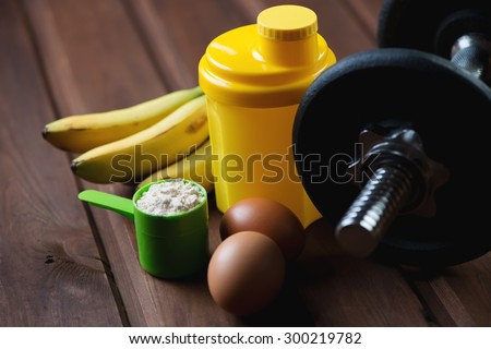 Shaker with a dumbbell, protein and protein food, close-up
