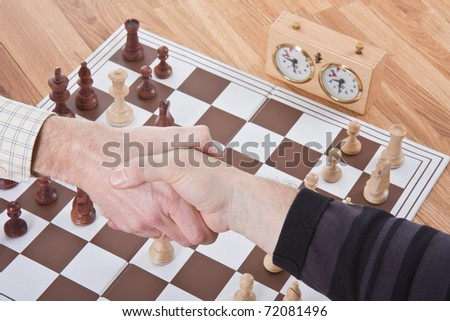 Shaking hands by the end of a chess match - stock photo