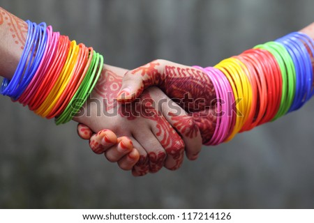 Shaking hands decorated with colorful bracelets and henna tattoo in Indian subcontinent - stock photo