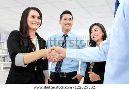 Shaking hands of two business people in the office - stock photo