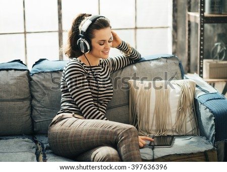 Shaking up time! Happy young woman choosing track on tablet PC while sitting on the couch in headphones in loft apartment - stock photo