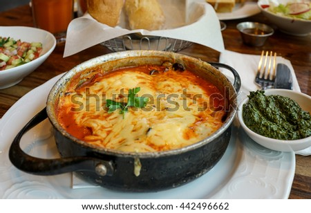 Shakshouka -  a dish of eggs poached in a sauce of tomatoes, chili peppers, and onions. It is believed to have a Jewish, Tunisian and Libyan origin.  Selective focus. - stock photo