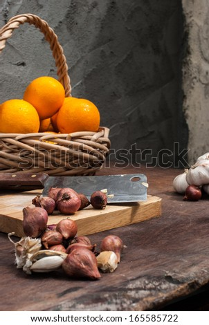 Shallots , Onion , Garlic , Chopping board , Knife , Orange with basket on the table - stock photo