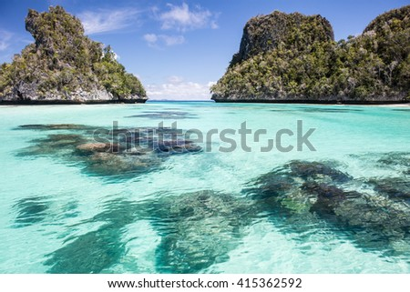 Shallow coral bommies are found near limestone islands in Wayag, Raja Ampat. This remote island group is surrounded by rich reefs and large schools of fish. - stock photo