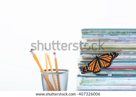 Shallow depth of field catches one monarch butterfly with open wings climbing up a pile of children's books. A finishing touch with pencils faded in the white background. Horizontal with copy space - stock photo