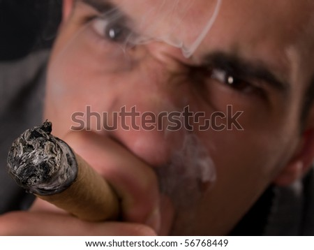 shallow depth of field image of angry male smoking Cuban cigar focus is on burning cigar tip - stock photo