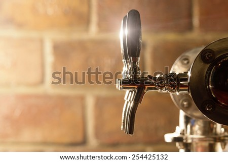 Shallow depth of field shot of beer tap machine with bricks in the background. - stock photo