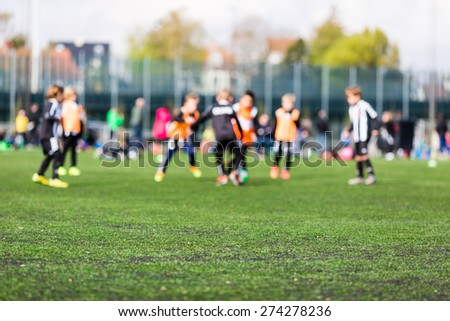 Shallow depth of field shot of young boys playing a kids soccer match on green turf. - stock photo