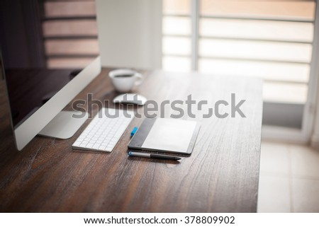 Shallow depth of field view of the workspace of a retoucher or illustrator with plenty of copy space - stock photo