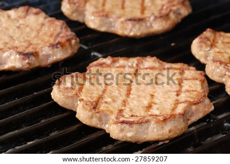 shallow DOF of hamburgers on a barbecue grill - stock photo