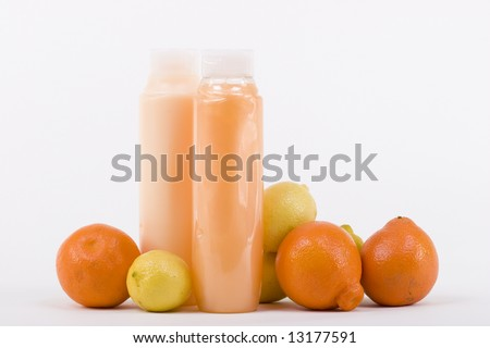 Shampoo and conditioner in bottles with few lemons and oranges - stock photo
