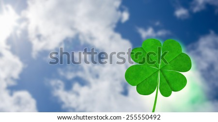 Shamrock against bright blue sky with clouds - stock photo