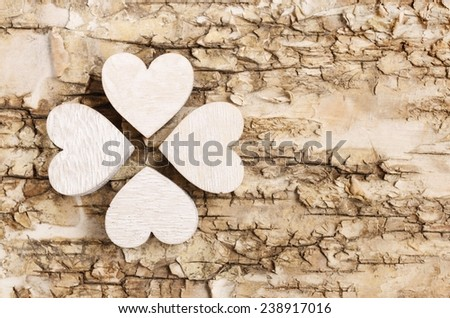 Shamrock (clover) made of wooden hearts on bark background. Symbol of luck - stock photo