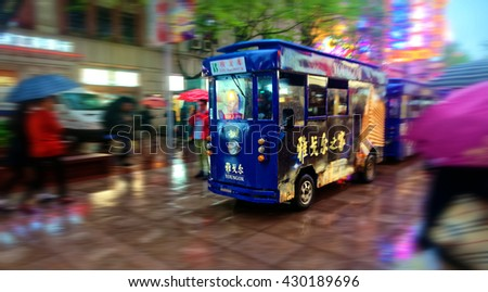 SHANGHAI, CHINA - April 20, 2016: A small sightseeing tourist train at Nanjing Road on a rainy Shanghai night.