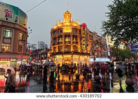 SHANGHAI, CHINA - April 20, 2016: Rainy Night in Busy Street of Shanghai. Shanghai weather is mild and moist, with a warm spring, a hot rainy summer, a cool autumn and an overcast cold winter.