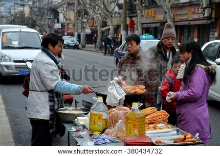 Shanghai, China - February 17, 2013: A Chinese man prepares fried street food from his mobile stall on a street in Shanghai. Patrons are seen around his stall waiting to receive their portions. - stock photo