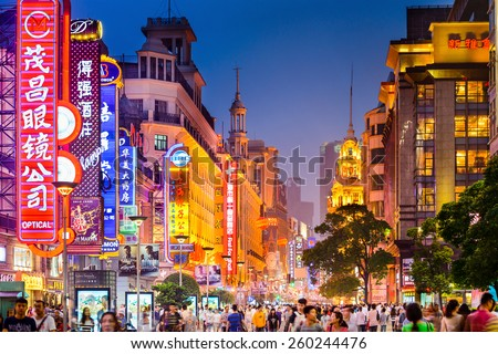 SHANGHAI, CHINA - JUNE 16, 2014: Neon signs lit on Nanjing Road. The area is the main shopping district of the city and one of the world's busiest shopping streets. - stock photo