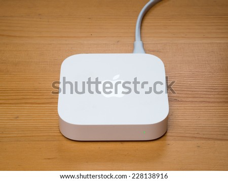 SHANGHAI, CHINA - MARCH 2014: An AirPort Express sits on the desk. The redesigned AirPort Express has been released by Apple in 2012. - stock photo
